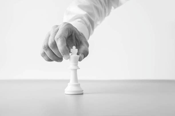 Greyscale image of a businessman placing a king chess figure on a desk stock photo