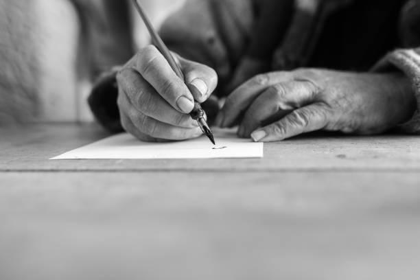 Graustufenbild eines älteren Mannes Kalligraphie zu tun – Foto