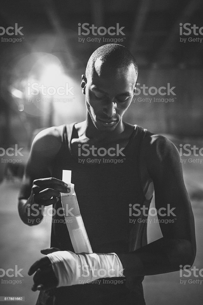 Greyscale image of afro-american boxer wrapping his hands stock photo