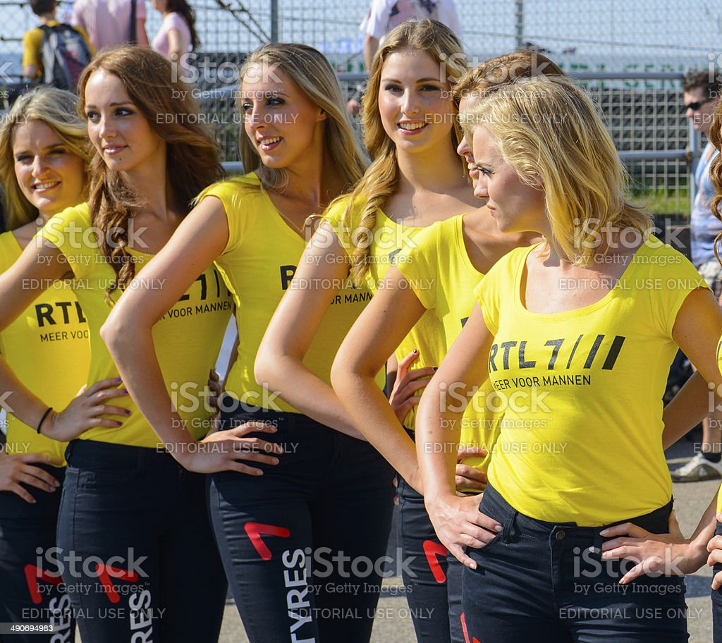 Grid girls posing in a row in the paddock stock photo