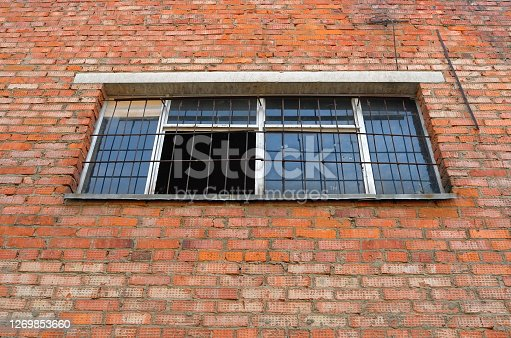 Grilled window in the brick wall
