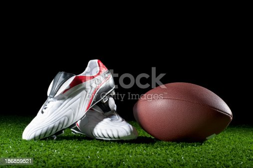 Gridiron ball and boots on grass at night