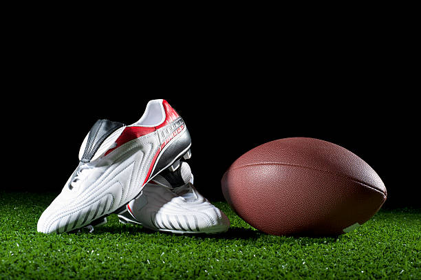 Gridiron ball and boots on grass Gridiron ball and boots on grass at night studded stock pictures, royalty-free photos & images