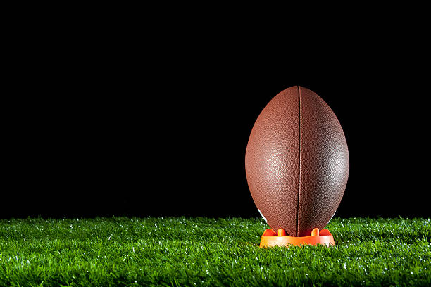 Gridiron ball standing on a tee Gridiron ball standing on a tee on the grass at night football lineman stock pictures, royalty-free photos & images