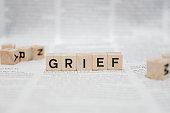 istock Grief Word Written In Wooden Cube - Newspaper 1141959171