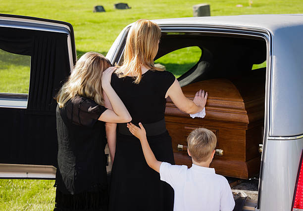 Grieving Family at a Funeral A woman and two children standing behind an open hearse. mourner stock pictures, royalty-free photos & images