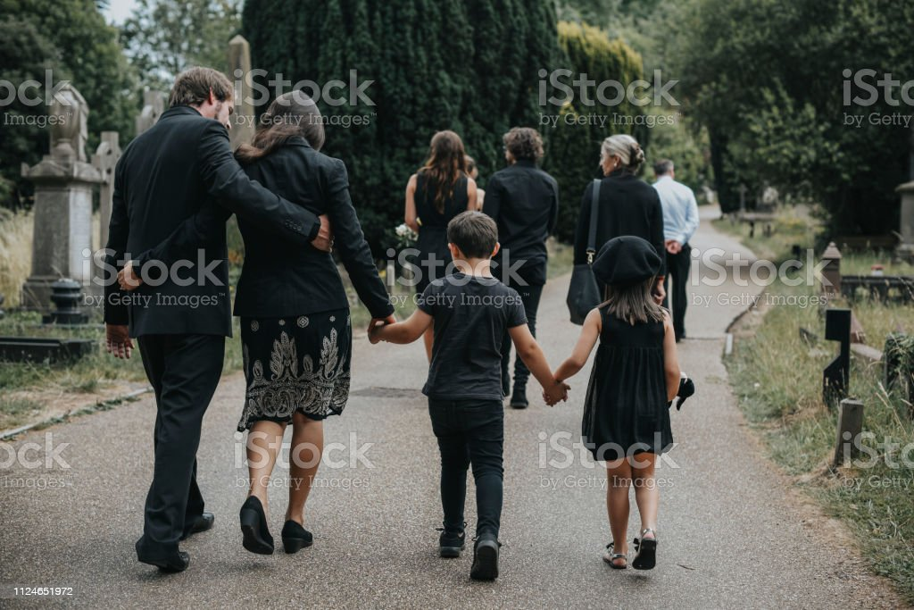 Grieving family walking through a cemetery Grieving family walking through a cemetery Adult Stock Photo