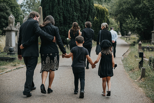 Grieving Family Walking Through A Cemetery Stock Photo - Download Image Now