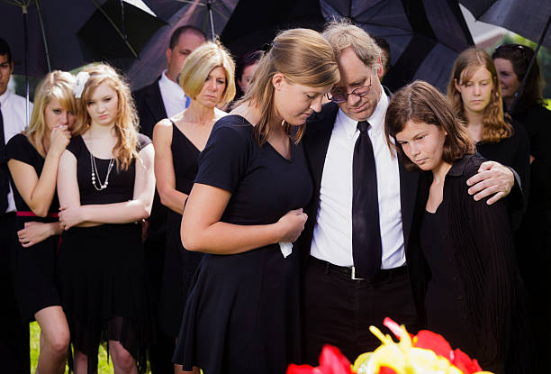 grieving father and daughters - funeral crying stockfoto's en -beelden