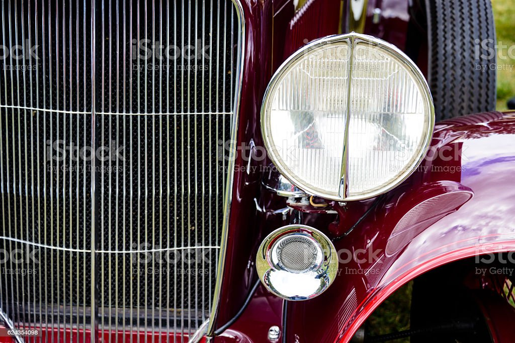 Grill of an antique red car with front head light stock photo