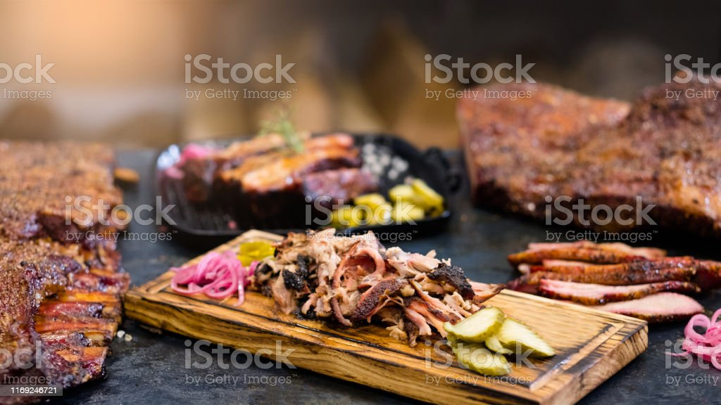 grill restaurant smoked pulled pork ribs meat ribs Grill restaurant. Closeup of smoked pulled pork served with pickles on wooden board. Roasted meat and ribs in background. American Culture Stock Photo