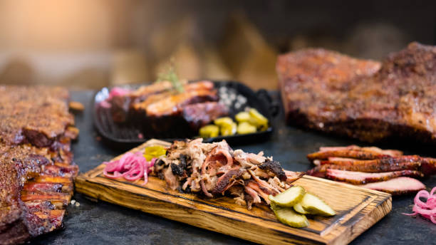 grill restaurant smoked pulled pork ribs meat ribs Grill restaurant. Closeup of smoked pulled pork served with pickles on wooden board. Roasted meat and ribs in background. southern usa stock pictures, royalty-free photos & images