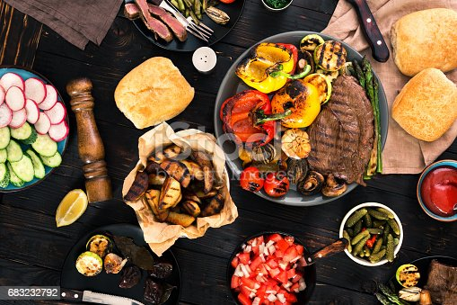 685404620istockphoto Grill table concept. Different foods cooked on the grill on the wooden table, grilled steak and grilled vegetables 683232792
