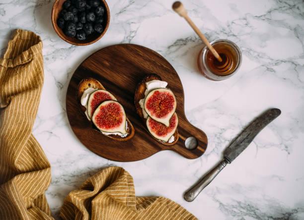 faire griller les toasts avec miel, fromage à la crème ou ricotta et figues mûres fraîches sur planche à découper. - figue photos et images de collection