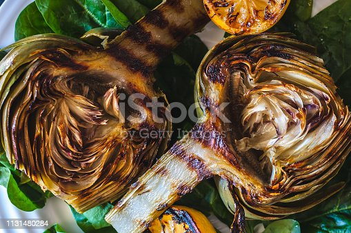 Grilled artichokes on a bed of spinach with grilled lemon halves