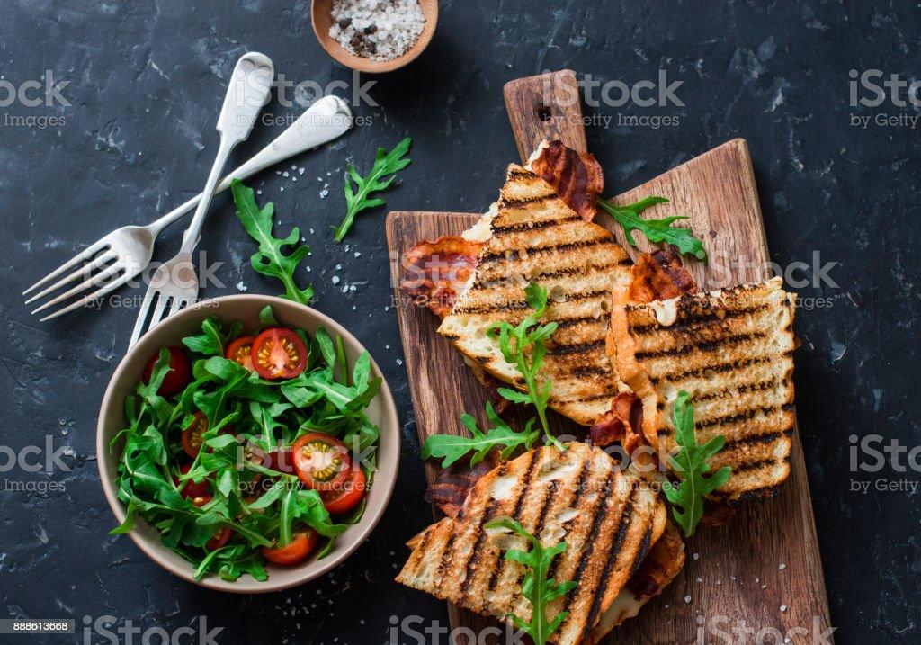 Gegrillter Speck, Brötchen Mozzarella auf Holz Schneidbretter und Rucola, Cherry-Tomaten-Salat auf dunklem Hintergrund, Ansicht von oben. Leckeres Frühstück oder Snack, flach legen – Foto