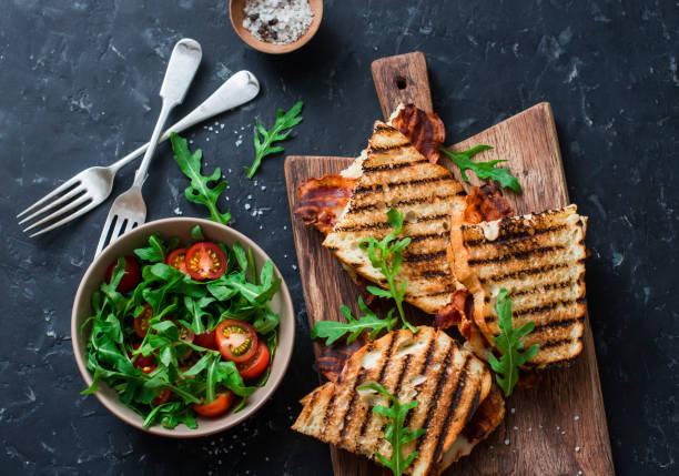 grilled bacon, mozzarella sandwiches on wooden cutting boards and arugula, cherry tomato salad on dark background, top view.delicious breakfast or snack, flat lay - panino ripieno foto e immagini stock