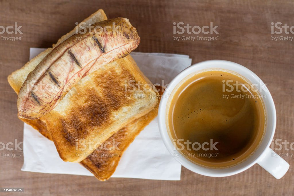 Grilled banana and slices two toast bread on white coffee cup for breakfast. royalty-free stock photo