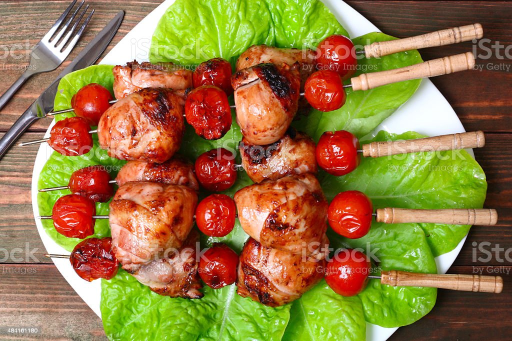 grilled barbecue kebab chicken legs and tomatoes on skewers stock photo