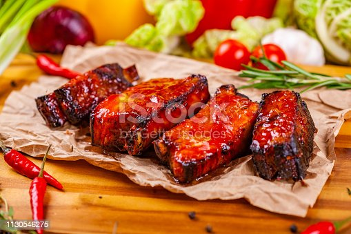 Grilled barbecue pork ribs with spices and herbs on wooden board