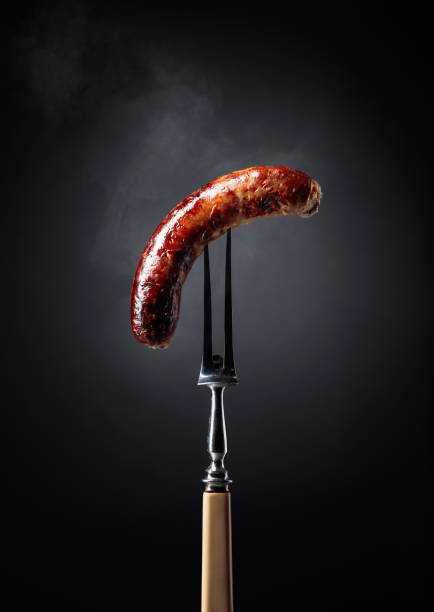 Grilled Bavarian sausage on a fork. stock photo