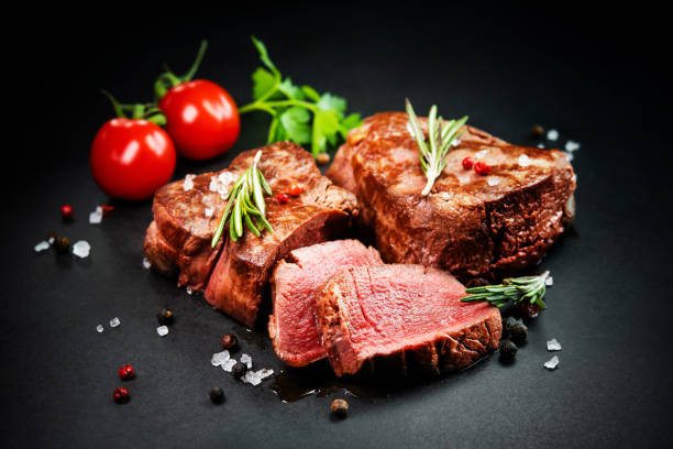Grilled beef filet steaks with herbs and spices on dark slate stock photo