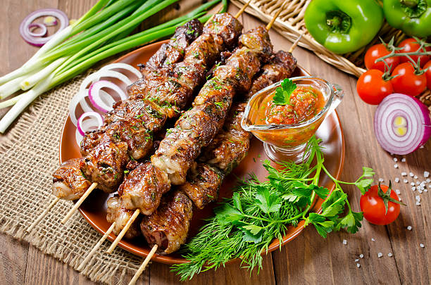 Grilled beef liver kebabs on a dark wooden background stock photo