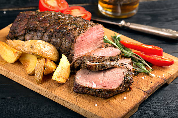 Grilled beef on a cutting board Grilled beef on a cutting board with potatoes and vegetables roast beef stock pictures, royalty-free photos & images