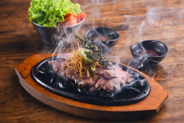 gegrilltes rindfleisch auf heißen stein mit rauch - grillstein stock-fotos und bilder
