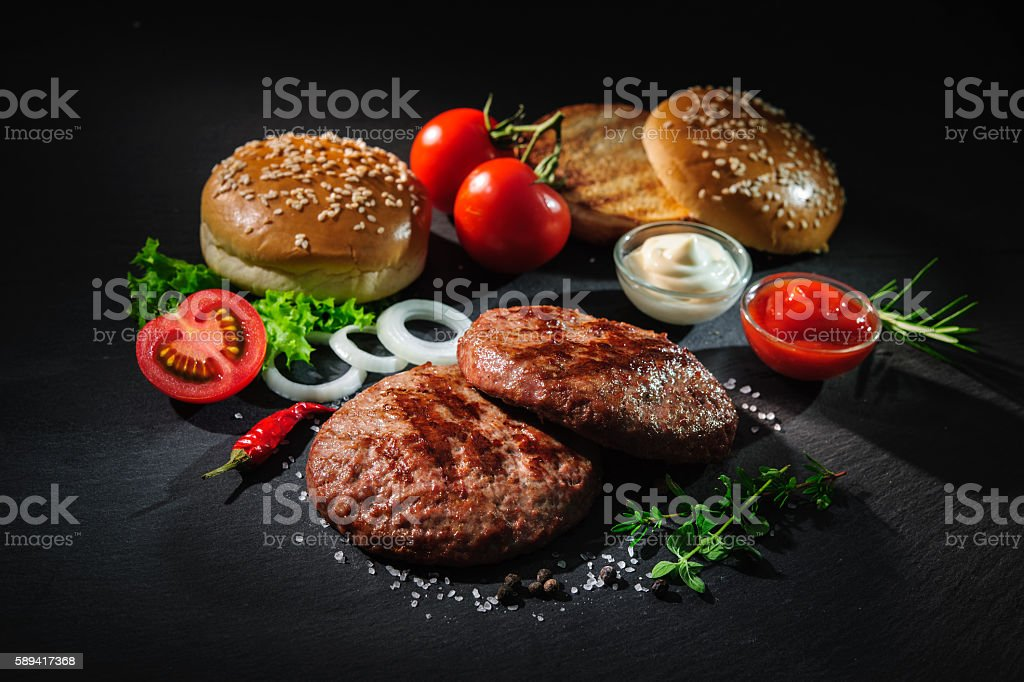 Grilled beef patties with other ingredients for hamburgers stock photo