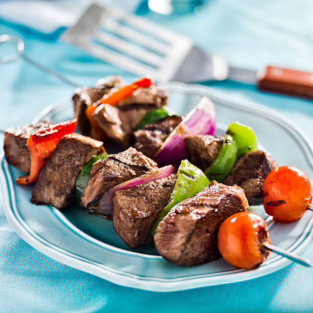 Grilled beef shish-kabobs with vegetables on a blue table stock photo