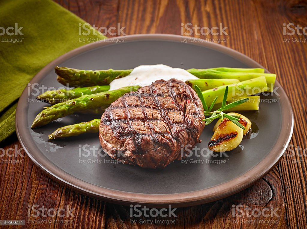 grilled beef steak and asparagus on dark plate stock photo