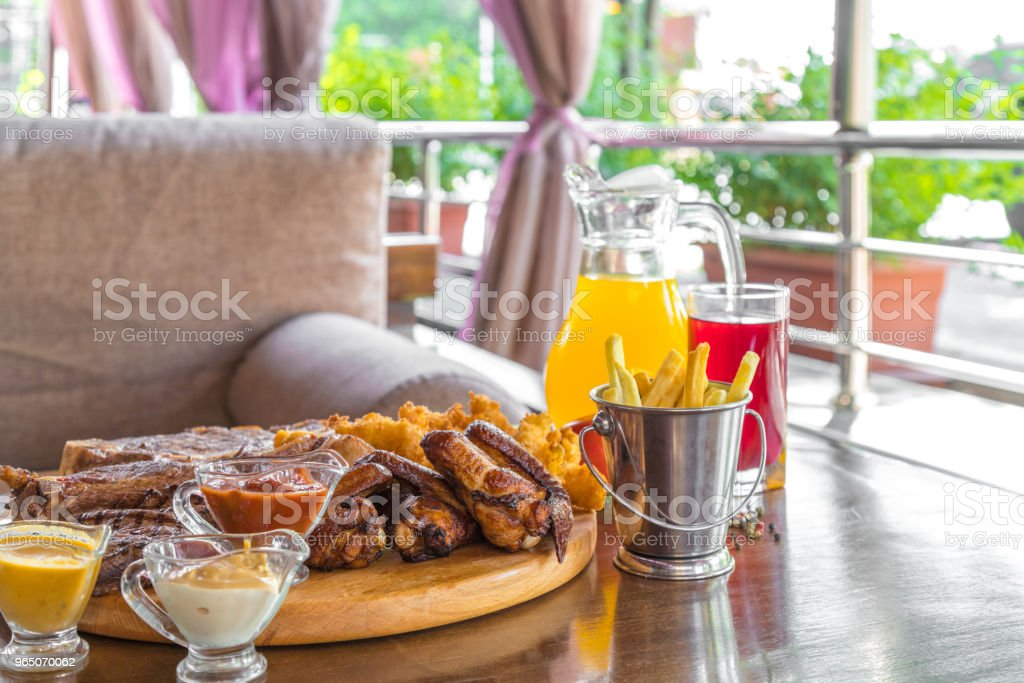 Grilled beef steak and Assorted delicious grilled meat with and cool drinks on the table of the summer veranda royalty-free stock photo