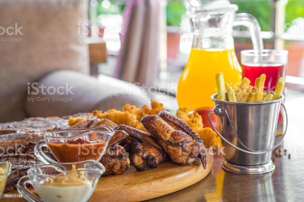Grilled beef steak and Assorted delicious grilled meat with french fries and cool drinks on the table of the summer veranda royalty-free stock photo