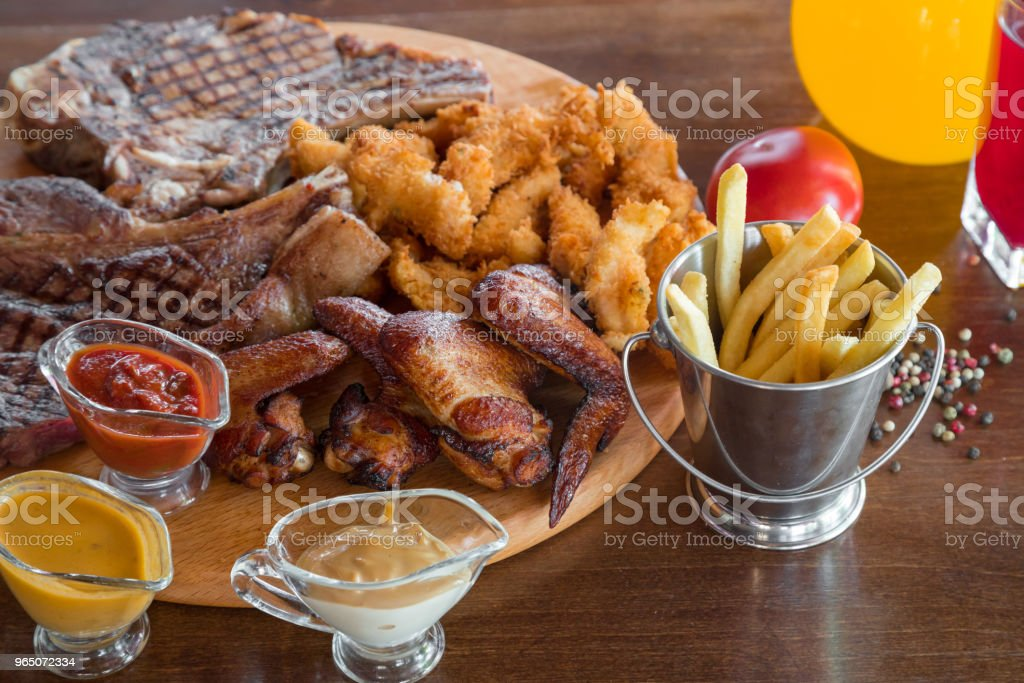 Grilled beef steak, chicken wings and assorted meat with french fries and sauces on cutting. Top view royalty-free stock photo