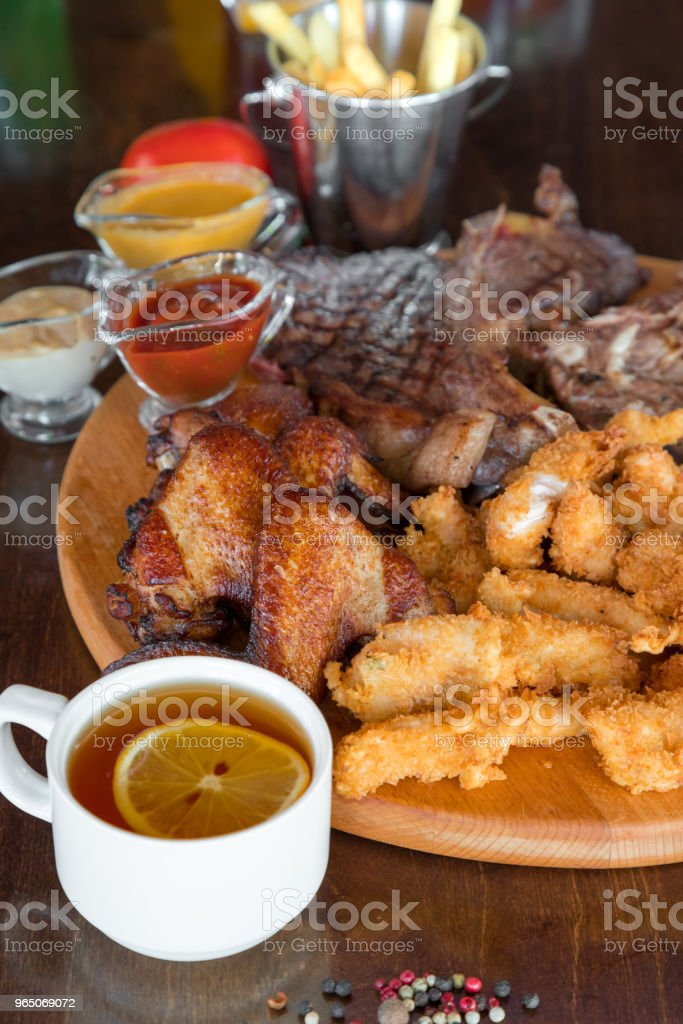 Grilled beef steak, chicken wings and breaded chicken sticks with french fries and sauces on cutting. Top view royalty-free stock photo