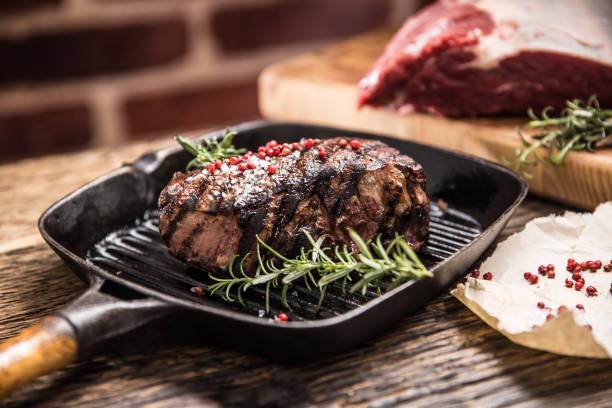 Gegrilltes Rindersteak in Grillpfanne mit Kräutern Rosmarin auf Holztisch – Foto