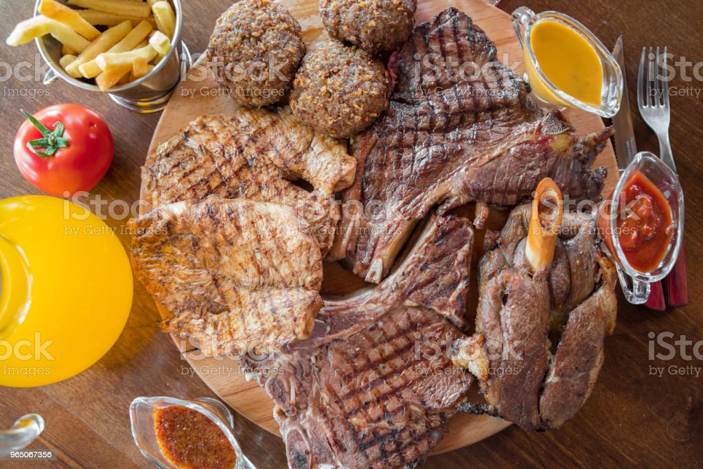 Grilled beef steak, lamb, cutlets with french fries and sauces on on wooden cutting board. Top view. zbiór zdjęć royalty-free