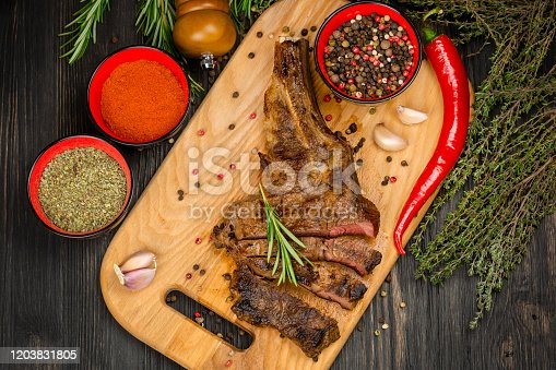 916096852 istock photo Grilled beef steak medium rare on wooden cutting board with chili pepper, spices and herbs 1203831805