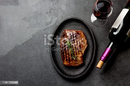 istock Grilled beef steak on black cast iron plate with red wine. Background with copy space. Barbecue, bbq meat beef tenderloin. Top view, slate background 1161700088