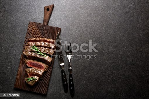 istock Grilled beef steak on cutting board with rosemary and spices. Rare steak top view 901284526
