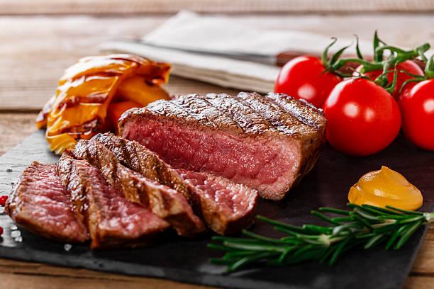 grilled beef steak rare sliced with vegetables - sirloin stockfoto's en -beelden