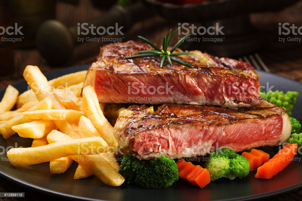 Grilled beef steak served with French fries and vegetables stock photo