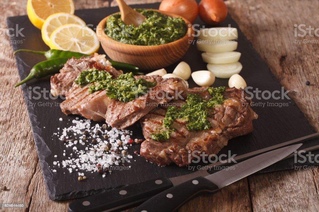 a la parrilla bistec con salsa de chimichurri en tablero de pizarra. horizontal - foto de stock