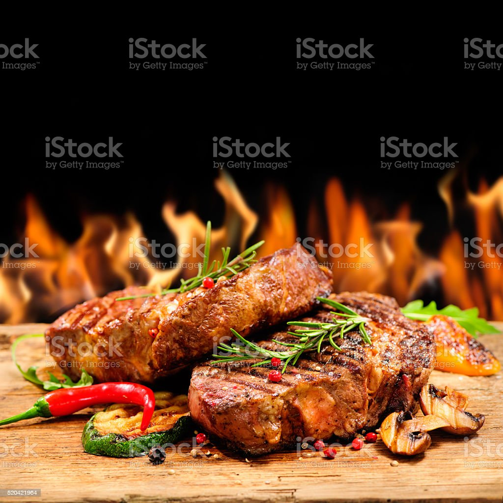 Grilled beef steak with flames stock photo