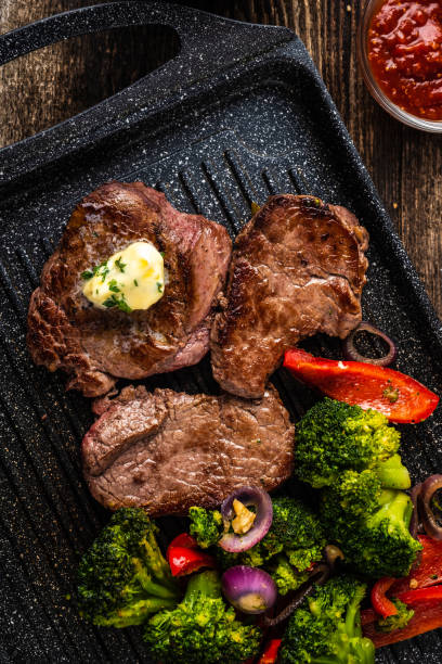 Cтоковое фото Grilled Beef steak with garlic butter and vegetables. Meat with grilled bell pepper, broccoli and onions.
