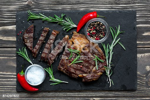 655794674 istock photo Grilled beef steak with herbs and spices on black slate cutting board 874297822