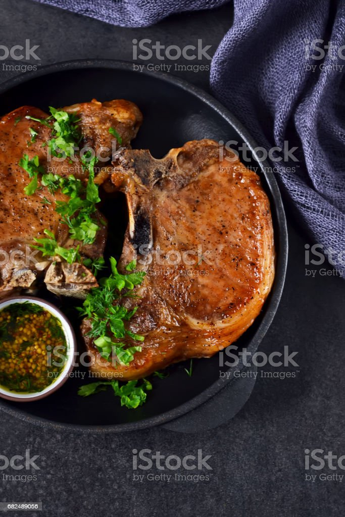 Grilled beef steak with mustard sauce in a cast-iron frying pan on a black background Стоковые фото Стоковая фотография