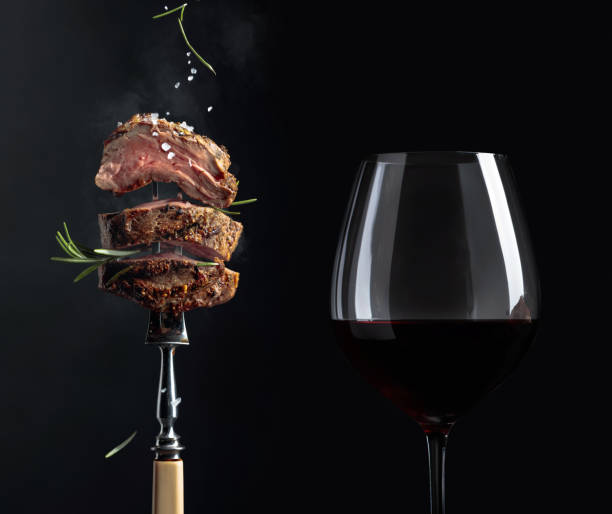 Grilled  beef steak with rosemary and glass of red wine on a black background. stock photo