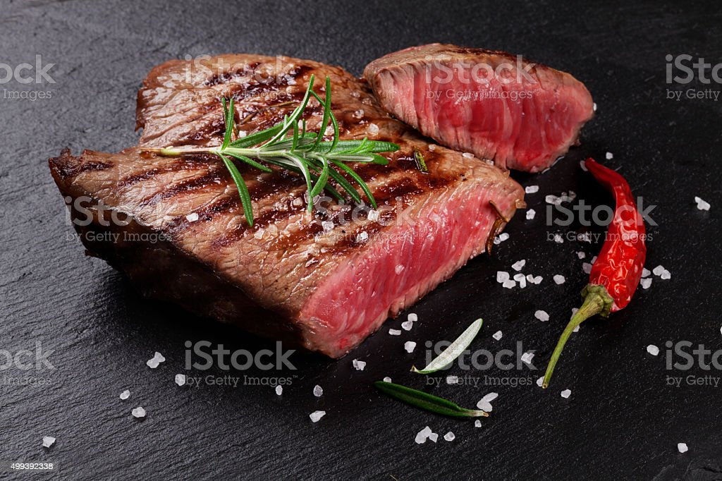 Grilled beef steak with rosemary, salt and pepper stock photo